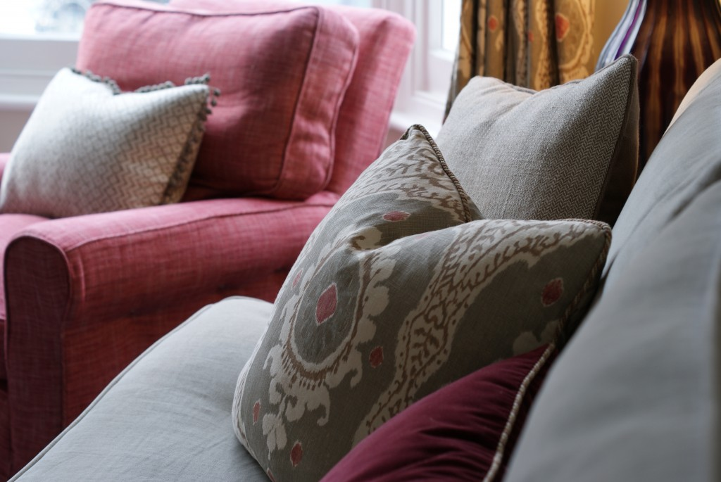 Pink armchair, grey linen sofa and pink and grey ikat print cushion.