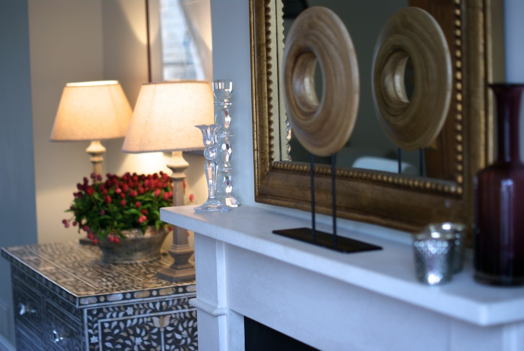 White wooden mantle piece with wooden circular objet and gilt mirror.
