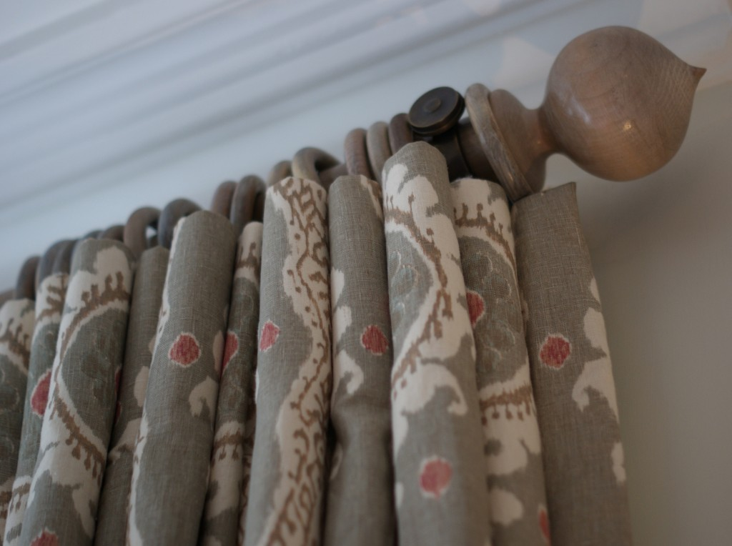 Bespoke limed oak curtain pole with pointed finial and grey and pink ikat curtains