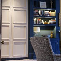 Panelled doors and Stifkey Blue walls with lit alcove shelving.