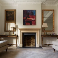 Limestone fireplace with red and blue oil painting above, parquet flooring and antique console and lamps.