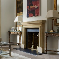 Limestone fireplace with oil painting above, gilt mirrors and antique consoles.