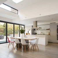White handleless Baulthaup kitchen with king table and chairs.