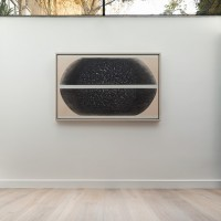 Contemporary black and white artwork on white wall.