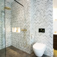 Mandarin stone marble zig zag tile in ensuite bathroom with polished brass Vola brassware