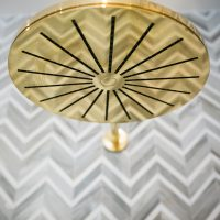 Polished brass Vola shower head and marble zig zag tile.