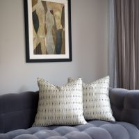 Grey velvet buttoned Roche Bobois sofa with green print silk cushions and artwork above.