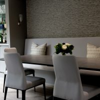 Ceramic dining table Roche Bobois with upholstered dining chairs and fitted leather bench seating.