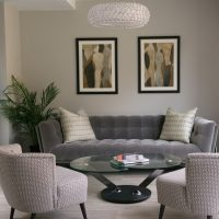 Contemporary sitting room with Roche Bobois buttoned back sofa, glass oval coffee table and green and grey prints on wall.