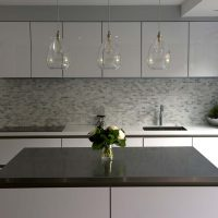 Hand blown glass pendants over island with black work top.