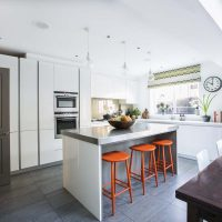White handleless kitchen with orange bar stools