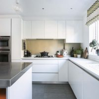 White handleless kitchen with stainless steel work top