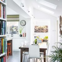 White handleless kitchen with side return showing wooden kitchen table and bookshelves.