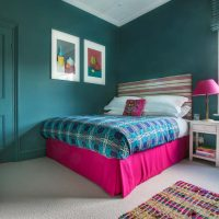 Teal blue childrens bedroom with pink valance, pink striped headboard and pink lamp