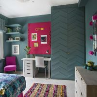 Teal blue childrens bedroom with pink pinboard and bespoke wardrobe with zig zag relief.
