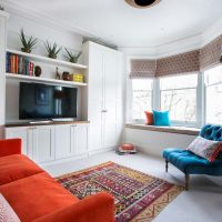 Orange and turquoise playroom scheme with orange sofa, orange and yellow kilim rug and turquoise buttoned back chair.