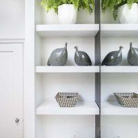 White bathroom shelving with plant and ornament.