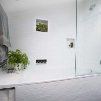 Bathroom with white Fired Earth metro tiles and niches in the wall.