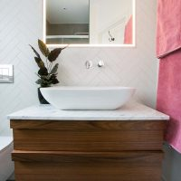 Bespoke walnut bathroom vanity Ealing with white herringbone wall tiles.
