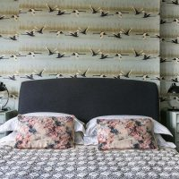 Flying duck print wallpaper in Ealing master bedroom with grey wool bedhead and pink and grey printed cushions