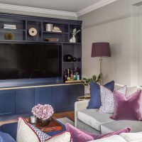 Snug TV room with grey velvet sofa, dark blue bespoke TV joinery with brass trim and navy and aubergine accent colours.