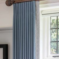 Blue wool full length curtains with Greek Key trim down leading edge on bespoke wooden pole.
