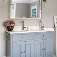 Blue grey hand painted panelled double bathroom vanity with limestone top, under counter basins and gilt mirror above.