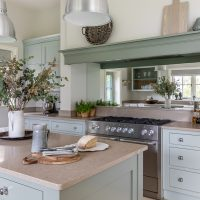 Country style hand painted shaker kitchen in light blue and duck egg with stainless steel range cooker and mirrored splash back.