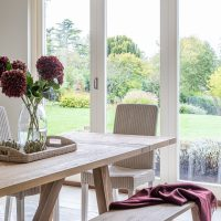 Large oak kitchen table with rattan chair and bench and views over the garden.
