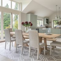 View of kitchen with large oak table with pale rattan chairs looking looking towards pale green hand painted shaker style kitchen.