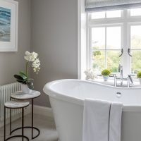 Large free standing bath with views over the garden. Antique bronze tables with a white orchid.