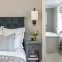 Grey upholstered buttoned headboard with blue painted bedside tables, bronze wall lights with cream shades and views into the ensuite bathroom with freestanding bath.