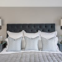 Upholstered dark grey button back headboard with bronze wall lights and cream silk shades, grey silk quilted bedspread and blue patterned cushions.