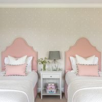 Girls bedroom with pink upholstered beds heads with grey butterfly wallpaper.