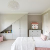 Girls room with pink upholstered beds, grey butterfly wallpaper and white feather pendant. Bespoke joinery with recess for books and toys.