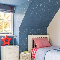 Boys bedroom with blue and gold star wallpaper and blue blind with red trip. Red and white checked bed linen.