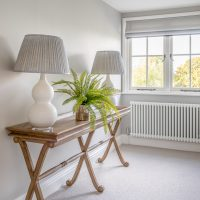 Large airy landing with oak console table, white curved lamp bases and grey Fermoie lamp shades.