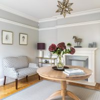 Large spacious hallway with oak circular table, upholstered sofa, parquet flooring and brass star pendant shade.