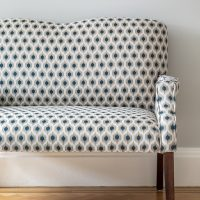 Small upholstered sofa in blue and grey print fabric with curved back