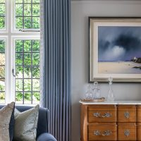 Blue wool full length curtains with dramatic blue landscape artwork and walnut chest of drawers with marble top.
