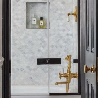 Marble scallop tiled bathroom with un lacquered brassware and black edged shower screen.