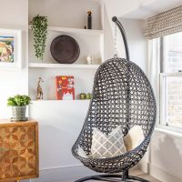 Black wicker egg shaped hanging chair in playroom with marquetry side board and shelves displaying books and toys.