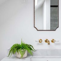 Marble topped bespoke vanity with un-lacquered brass taps and slim black oval framed mirror above.