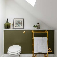 Olive green painted concealed cistern in bathroom with un lacquered brass towel rail