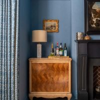 Antique inlaid drinks cabinet with marble lamp and drinks tray. Blue linen wallpaper and hand printed curtains.