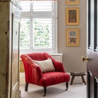 Red kilim upholstered armchair with antique Indian prints on the wall and antique Scandinavian wardrobe.