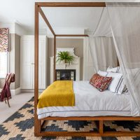 Teak four poster bed with yellow blanket and black and sisal rug. Square bay window with mulitcoloured stitched roman blinds.