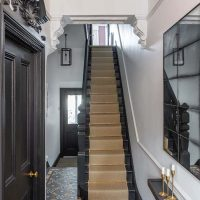 Black and white hallway with sisal runner and tiled floor