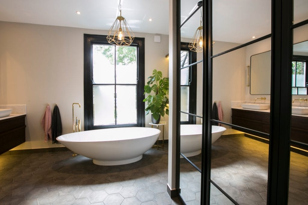 Volcanic stone freestanding bath with hexagonal floor tile and black accents