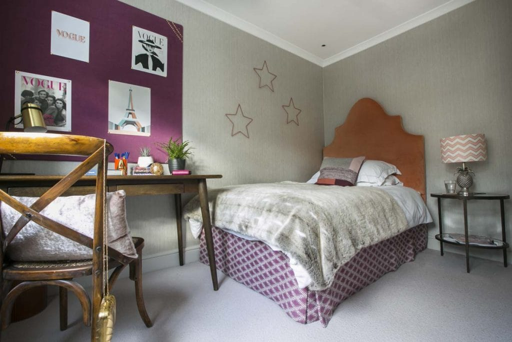 Teenage girls bedroom with coral velvet headboard and plum coloured pinboard